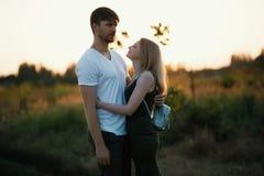 Pares románticos en la puesta del sol Dos personas en amor en la puesta del sol o la salida del sol Hombre y mujer en campo Fotografía de archivo
