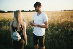 Pares románticos en la puesta del sol Dos personas en amor en la puesta del sol o la salida del sol Hombre y mujer en campo Foto de archivo