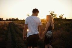 Pares románticos en la puesta del sol Dos personas en amor en la puesta del sol o la salida del sol Hombre y mujer en campo Imagen de archivo