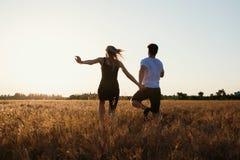 Pares románticos en la puesta del sol Dos personas en amor en la puesta del sol o la salida del sol Hombre y mujer en campo Imágenes de archivo libres de regalías