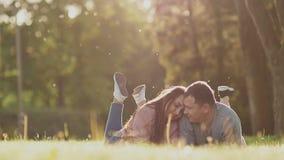 Pares románticos en un claro verde en verano Mienten en sus estómagos con sus pies para arriba Feliz junto en los rayos de metrajes