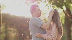 Pares románticos en un parque verde del verano Están cercanos el uno al otro Miran uno a en los rayos de la luz del sol almacen de metraje de vídeo