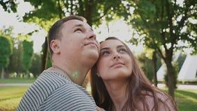 Pares románticos en un parque verde del verano Están cercanos el uno al otro Están mirando para arriba feliz junto Verano E almacen de video