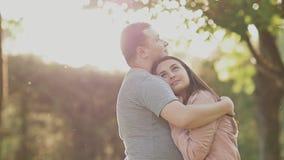 Pares románticos en un parque verde del verano Un individuo joven abraza a su muchacha en los rayos de la luz del sol feliz junto almacen de metraje de vídeo