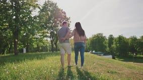 Pares románticos en un parque verde del verano Se toman por la mano y el paseo juntos en los rayos de la luz del sol Beso metrajes