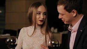 Pares románticos en un restaurante que mira el menú almacen de video