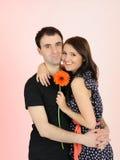 Pares románticos encantadores con el abarcamiento de la flor Imagenes de archivo