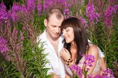 Pares románticos entre las flores púrpuras Fotos de archivo libres de regalías