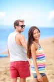 Pares románticos felices en la playa que lleva a cabo las manos Fotografía de archivo libre de regalías