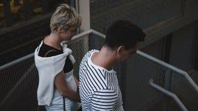 Pares románticos felices hermosos que van abajo de las escaleras metálicas de New York City que llevan a cabo las manos, disfruta metrajes