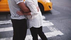 Pares románticos felices jovenes de la cámara lenta que se unen y que abrazan en el paso de peatones de Nueva York, coches que pa almacen de video