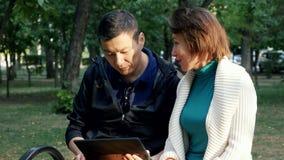 Pares románticos felices que se sientan en banco en el parque que sonríe usando la tableta almacen de metraje de vídeo