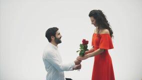 Pares románticos hermosos aislados en el fondo blanco Una mujer joven atractiva que lleva rosas rojas en un vestido y almacen de video