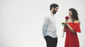 Pares románticos hermosos aislados en el fondo blanco Una mujer joven atractiva que lleva rosas rojas en un vestido y