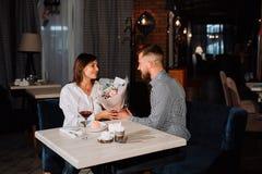 Pares románticos hermosos de la sorpresa en café El hombre joven está presentando las flores la suya querida Sensación de la feli imagenes de archivo