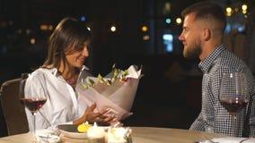 Pares románticos hermosos de la sorpresa en café El hombre joven está presentando las flores la suya querida Sensación de la feli almacen de video