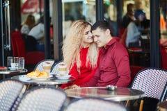Pares románticos hermosos en café al aire libre parisiense fotografía de archivo libre de regalías