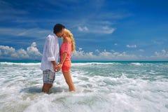 Pares románticos jovenes felices que se colocan en la playa y que besan el ea Imágenes de archivo libres de regalías