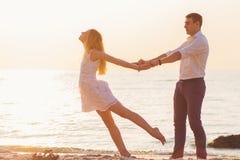 Pares románticos jovenes hermosos que llevan a cabo las manos en la playa en rayos Fotos de archivo libres de regalías