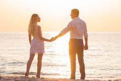 Pares románticos jovenes hermosos que llevan a cabo las manos en la playa en rayos Imágenes de archivo libres de regalías