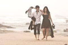 Pares románticos jovenes que caminan a lo largo de la playa Imágenes de archivo libres de regalías