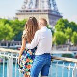 Pares románticos jovenes que miran la torre Eiffel en París, Francia Foto de archivo libre de regalías