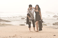 Pares románticos jovenes que salen a lo largo de la playa después de noche Foto de archivo