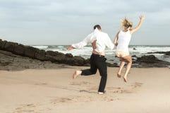 Pares románticos jovenes que saltan en la playa en la salida del sol imágenes de archivo libres de regalías