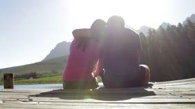 Pares románticos jovenes que se sientan en extremo del embarcadero de madera por el lago metrajes