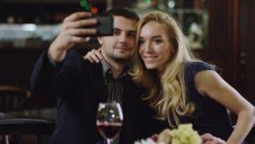Pares románticos jovenes que toman el selfie en restaurante almacen de metraje de vídeo