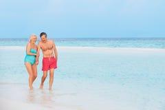 Pares románticos mayores que caminan en el mar tropical hermoso Imágenes de archivo libres de regalías