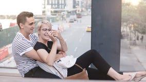 Pares románticos multiétnicos felices que se sientan en un puente de la calle de Nueva York, tomando el selfie del smartphone y t almacen de video