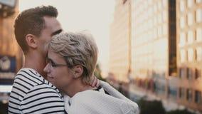 Pares románticos multiétnicos jovenes hermosos que se colocan y que abrazan en un puente de la puesta del sol de Nueva York que d metrajes