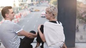 Pares románticos multiétnicos jovenes hermosos que se sientan en un puente, charlando, cabeceando y riendo sobre la calle de Nuev almacen de video
