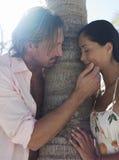 Pares románticos por el tronco de árbol en la playa Foto de archivo libre de regalías