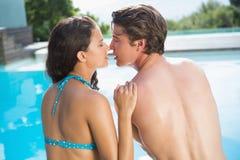 Pares románticos por la piscina en un día soleado Imagenes de archivo