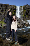 Pares románticos por una cascada Imagen de archivo libre de regalías