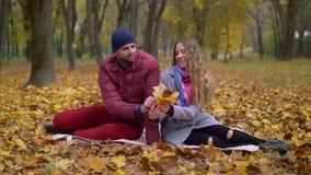 Pares románticos positivos que se relajan en parque del otoño almacen de video