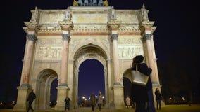 Pares románticos que abrazan cerca de Arc de Triomphe famoso du Carrousel, amor en París metrajes