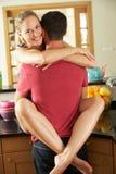 Pares románticos que abrazan en cocina Imágenes de archivo libres de regalías