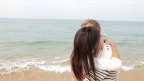 Pares románticos que abrazan y que se besan en la playa junto almacen de metraje de vídeo