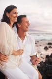 Pares románticos que beben Champán en la playa en la puesta del sol Fotografía de archivo