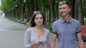 Pares románticos que caminan a lo largo de un parque metrajes