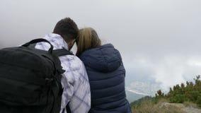 Pares románticos que caminan unirse en el pico de montaña que besa y que disfruta del paisaje impresionante - almacen de metraje de vídeo