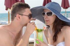 Pares románticos que comparten un cóctel tropical Foto de archivo