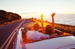 Pares románticos que conducen en el camino hermoso en la puesta del sol