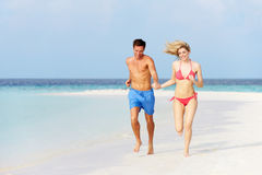 Pares románticos que corren en la playa tropical hermosa Foto de archivo