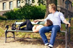 Pares románticos que descansan sobre el banco de parque Imagenes de archivo