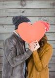 Pares románticos que llevan a cabo forma del corazón y que se besan Imagenes de archivo
