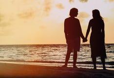 Pares románticos que llevan a cabo las manos en la playa de la puesta del sol Fotografía de archivo libre de regalías